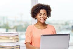 Mujer afroamericana feliz con el ordenador portátil en casa Foto de archivo libre de regalías