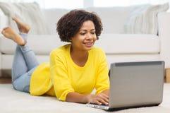 Mujer afroamericana feliz con el ordenador portátil en casa Foto de archivo