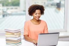 Mujer afroamericana feliz con el ordenador portátil en casa Fotos de archivo libres de regalías