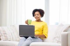 Mujer afroamericana feliz con el ordenador portátil en casa Imágenes de archivo libres de regalías