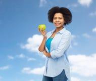 Mujer afroamericana feliz con la manzana verde fotografía de archivo