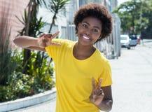 Mujer afroamericana feliz en una camisa amarilla Imagenes de archivo