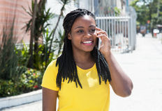 Mujer afroamericana feliz en una camisa amarilla en el teléfono móvil Fotografía de archivo