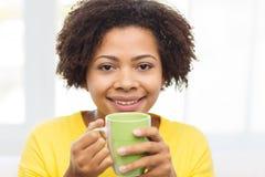 Mujer afroamericana feliz que bebe de la taza de té Imagen de archivo