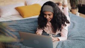 Mujer afroamericana feliz que miente en cama usando el ordenador portátil para hojear la web Muchacha que lleva la sonrisa rosada almacen de video