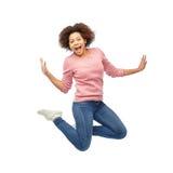 Mujer afroamericana feliz que salta sobre blanco Imagenes de archivo
