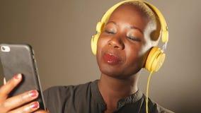 Mujer afroamericana feliz y atractiva joven con los auriculares amarillos y el teléfono móvil que escucha la sonrisa de la canció metrajes