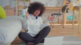 Mujer afroamericana hermosa con un peinado afro que se sienta en el piso con un ordenador portátil aprendido sobre el triunfo MES almacen de metraje de vídeo