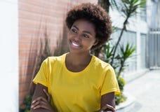 Mujer afroamericana hermosa en una camisa amarilla Imágenes de archivo libres de regalías