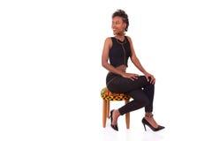 Mujer afroamericana hermosa que se sienta en un taburete aislado encendido Fotografía de archivo