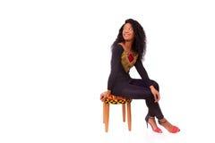 Mujer afroamericana hermosa que se sienta en un taburete aislado encendido Imagen de archivo