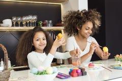 Mujer afroamericana hermosa y su hija que colorean los huevos de Pascua en la cocina Foto de archivo