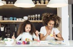 Mujer afroamericana hermosa y su hija que colorean los huevos de Pascua en la cocina Imagen de archivo