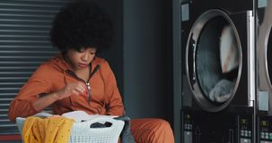 Mujer afroamericana joven cansada que lee un libro mientras que lava su lavadero en la lavandería Ella bosteza y espera metrajes