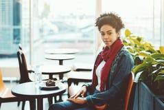 Mujer afroamericana joven en café de la oficina con la torta Imagen de archivo libre de regalías