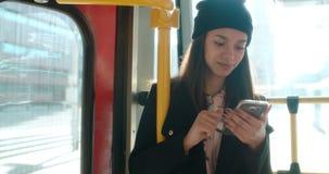 Mujer afroamericana joven en el tren usando el teléfono Imágenes de archivo libres de regalías