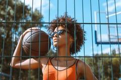 mujer afroamericana joven en sujetador de los deportes y gafas de sol que sostienen una bola del baloncesto en su hombro, present Fotos de archivo libres de regalías