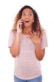 Mujer afroamericana joven extática que hace una llamada de teléfono en ella Imagenes de archivo
