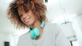 Mujer afroamericana joven feliz con los auriculares que presentan a una cámara Fotos de archivo