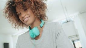 Mujer afroamericana joven feliz con los auriculares que presentan a una cámara metrajes