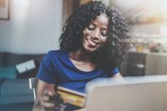 Mujer afroamericana joven feliz que hace compras en línea a través del ordenador portátil usando tarjeta de crédito en casa Horiz imagen de archivo libre de regalías