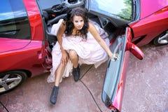 Mujer afroamericana joven hermosa en un coche de deportes del rojo Foto de archivo