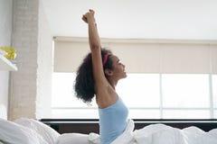 Mujer afroamericana joven hermosa que despierta en cama Imagen de archivo