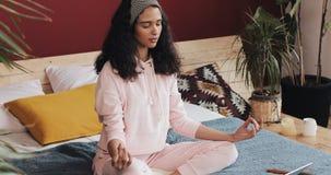 Mujer afroamericana joven hermosa que hace ejercicio de la yoga y que mira la lección preceptoral en el ordenador portátil en cas almacen de video
