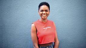 Mujer afroamericana joven hermosa que sonríe en la cámara que parece confiada metrajes