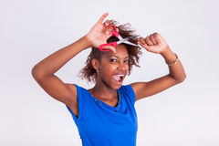 Mujer afroamericana joven que corta su pelo afro muy rizado con s Foto de archivo libre de regalías