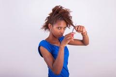 Mujer afroamericana joven que corta su pelo afro muy rizado con s Fotos de archivo