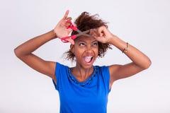Mujer afroamericana joven que corta su pelo afro muy rizado con s Imagen de archivo