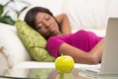 Mujer afroamericana joven que duerme en el sofá Fotografía de archivo libre de regalías