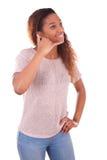Mujer afroamericana joven que hace una llamada de teléfono en su smartpho Fotos de archivo libres de regalías