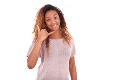 Mujer afroamericana joven que hace una llamada de teléfono en su smartpho Imágenes de archivo libres de regalías