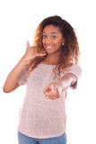 Mujer afroamericana joven que hace una llamada de teléfono en su smartpho Foto de archivo libre de regalías
