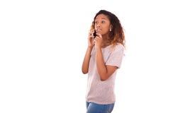 Mujer afroamericana joven que hace una llamada de teléfono en su smartpho Fotografía de archivo libre de regalías