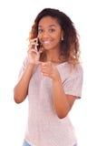 Mujer afroamericana joven que hace una llamada de teléfono en su smartpho Imagen de archivo