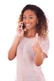 Mujer afroamericana joven que hace una llamada de teléfono en su smartpho Fotos de archivo