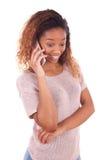 Mujer afroamericana joven que hace una llamada de teléfono en su smartphone Fotos de archivo libres de regalías