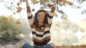 54f0f8f47e6c8 Mujer afroamericana joven que lanza las hojas otoñales para arriba en  parque almacen de metraje de