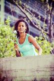 Mujer afroamericana joven que le falta con la rosa del blanco en nuevo Fotos de archivo libres de regalías