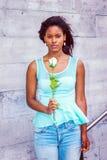 Mujer afroamericana joven que le falta con la rosa del blanco en nuevo Fotografía de archivo