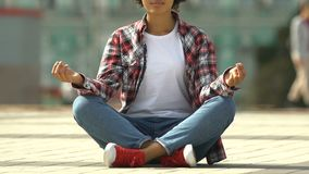 Mujer afroamericana joven que medita yoga en la posición de loto respecto a la calle urbana ocupada almacen de video