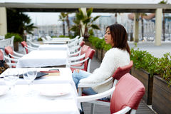 Mujer afroamericana joven que se sienta en la tabla de restaurante hermoso del aire abierto fotos de archivo