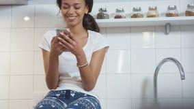Mujer afroamericana joven que se sienta en una cocina y que mecanografía en el teléfono móvil almacen de video