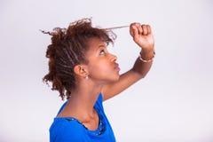 Mujer afroamericana joven que se sostiene el pelo afro muy rizado - Blac Fotografía de archivo