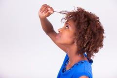 Mujer afroamericana joven que se sostiene el pelo afro muy rizado - Blac Fotos de archivo