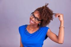 Mujer afroamericana joven que se sostiene el pelo afro muy rizado - Blac Foto de archivo libre de regalías