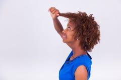 Mujer afroamericana joven que se sostiene el pelo afro muy rizado - Blac Fotografía de archivo libre de regalías